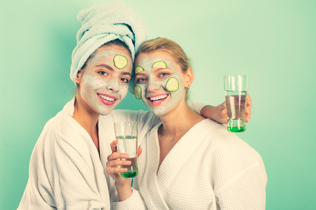 Girls friends sisters making clay facial mask. Anti age mask. Stay beautiful. Skin care for all ages. Women having fun cucumber skin mask. Relax concept. Beauty begins from inside. Spa and wellness