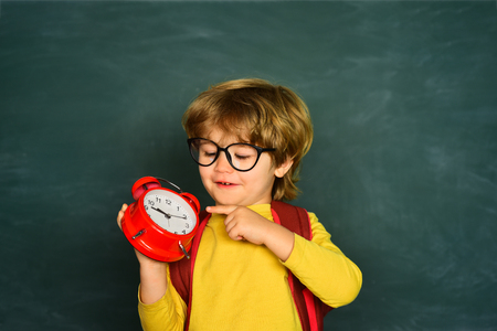 Back to school. Alarm clock anxiety. Late. Kid boy holding clock alarm.