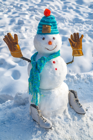 Cute little snowman outdoor. The snowman is wearing a fur hat and scarf. Snow man outdoor. Snowman isolated on snow background. Snowman in a scarf and hat.
