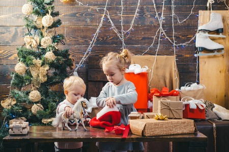 Children gift. Winter evening at home. Portrait of happy child looking at decorative toy ball by Christmas tree. Babies. Opening gifts on Christmas and New Year. Stok Fotoğraf