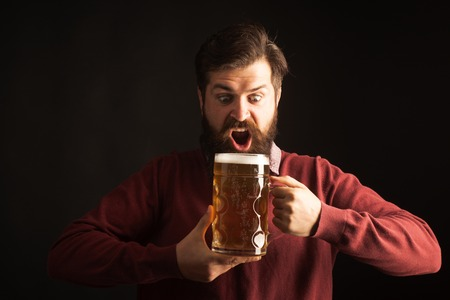 Emotional funny bearded drunk hipster holds craft bottled beer. Happy brewer. Bearded man with a glass of beer. Stock Photo