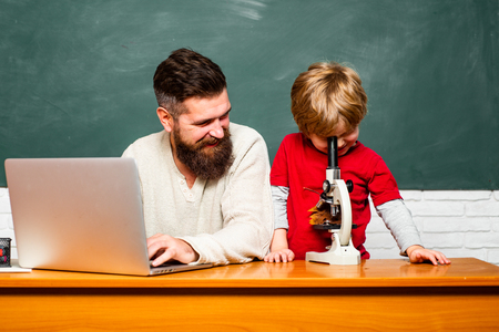 Elementary school teacher and student in classroom. Daddy play with schoolboy. Teacher and schoolboy using laptop in class. Teacher helping pupils studying on desks in classroom.