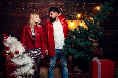 Christmas tree. Fashion couple over Christmas tree lights background. Having a crazy day with friend. Expression and people concept.