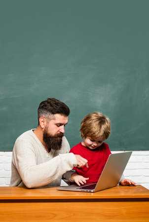 Teacher helping kids with their homework in classroom at school. Homeschooling. Man teacher play with preschooler child. Chalkboard background. Stock Photo