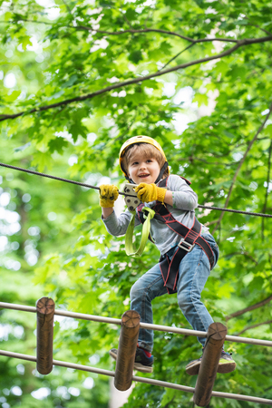 Child boy having fun at adventure park. Go Ape Adventure. Cargo net climbing and hanging log. Early childhood development. Artworks depict games at eco resort which includes flying fox or spider net. Stock Photo