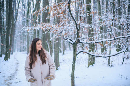 Portrait of a young woman in snow trying to warm herself. Beautiful girl in the winter forest in white down jacket. Banco de Imagens