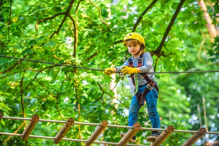 Kids boy adventure and travel. Adventure climbing high wire park. Early childhood development. Cute child in climbing safety equipment in a tree house or in a rope park climbs the rope