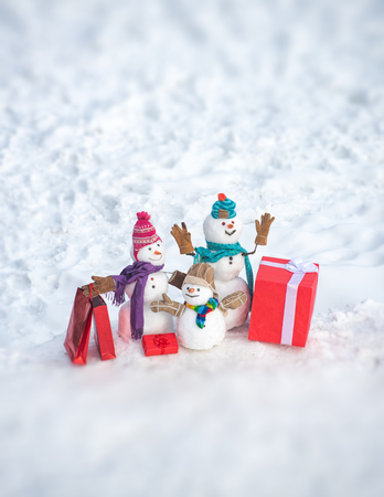 Christmas holidays discounts and winter sale. Happy winter snowman family. Funny snowman family in stylish hat and scarf on snowy field.
