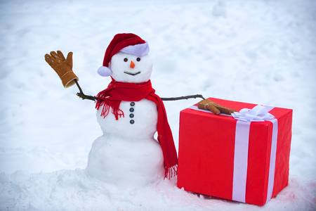 Snowman the friend is standing in winter hat and scarf with red nose. Christmas snowman on white snow background. Snow man with gift.