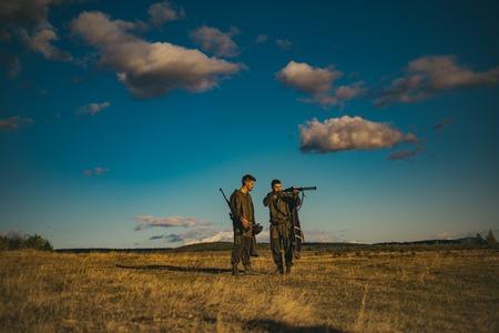 Hunters with shotgun gun on hunt. hunter man holding gun and walking in forest.