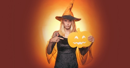 Glamour Fashion Sexy Vampire Lady with witch costume. Beautiful young surprised woman in witch hat and costume pointing hand - showing products. Attractive model girl in Halloween costume.