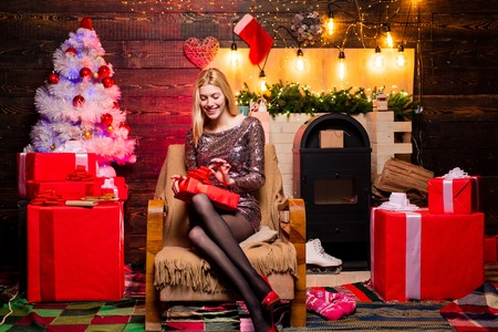Woman in red Santa hat holding present. Christmas preparation. Luxury girl celebrating New Year. Blonde Santa woman holding gift box at vintage wall. Christmas fashion.