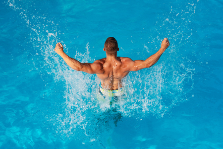 Summer vacation and travel to ocean. Athletic muscle trainer. Young man active leisure - swimming pool concept. Handsome guy resting while swimming pool outdoor.