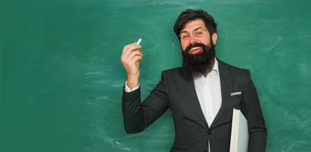 Teacher preparing for university exams. Back to school and happy time. Portrait of male University Student indoors. Young bearded teacher near chalkboard in school classroom.