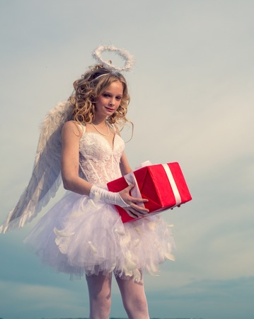 Lovely girl Cupid angel with gift with bow and arrow is ready to find your love. Portrait of little curly blond Angel girl. Cute teen Cupid angel with gift on the cloud - sky background. Stock Photo