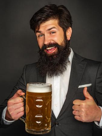 Emotional funny bearded drunk hipster holds craft bottled beer. Beard man drinking beer from a beer mug. Standard-Bild