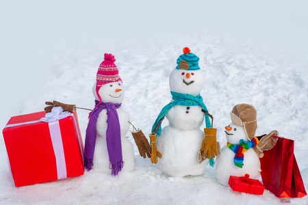 Snowman - father, mother and snowman - baby surprise outdoor. Greeting snowman family, parenthood concept. Delivery gifts. Banque d'images