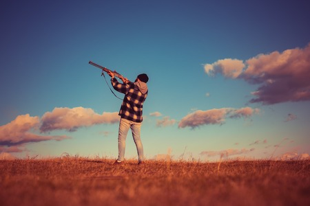 Skeet shooting. Hunter aiming rifle in forest. Hunter with shotgun gun on hunt. Hunting without borders. Process of duck hunting. Copy space for text.