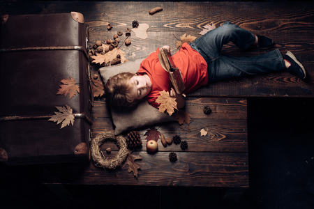 Cute little child boy are getting ready for autumn. Kid playing in autumn. Little cute boy lies on wooden floor with autumn leaves and read book. Biggest discounts for all autumn clothes for children.