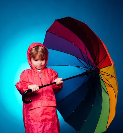 Little boy with rainbow-colored umbrella isolated on blue background. Kid in rain. Cute little child boy wearing in autumn clothes on autumn rain day. Cloud rain umbrella. Raining concept.