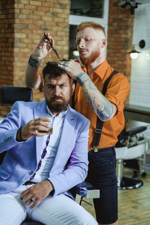Ideas about Barbershop and Barber salon. Brutal guy in modern Barber Shop. Hairdresser makes hairstyle a man with a beard. Barber - Shaves and Trims. Beard care.