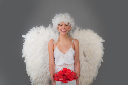Fallen white angel. Romantic young beauty as an angel. Angel with gift. Long white wings. Valentines Day concept. Happy Valentines Day. Stock fotó