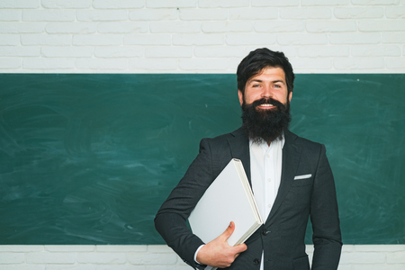 Tutoring. Back to school and happy time. Bearded professor at school lesson at desks in classroom. Teacher preparing for university exams. Friendly teacher in classroom near blackboard desk.