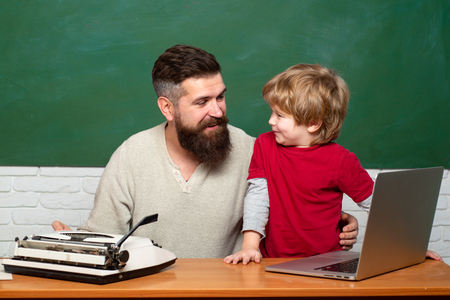 Back to school and Education concept. Elementary school teacher and student in classroom. Copy space. Teacher helping pupils studying on desks in classroom. Daddy Teacher.