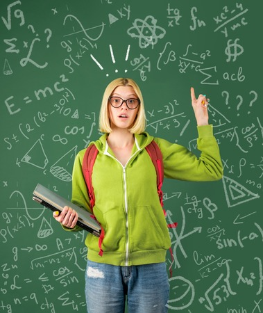 Back to school. Funny female young teacher in the classroom. Mark for exam.