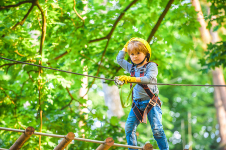 Cute child boy playing. Artworks depict games at eco resort which includes flying fox or spider net. Every childhood matters. Toddler age. Children fun Stock Photo
