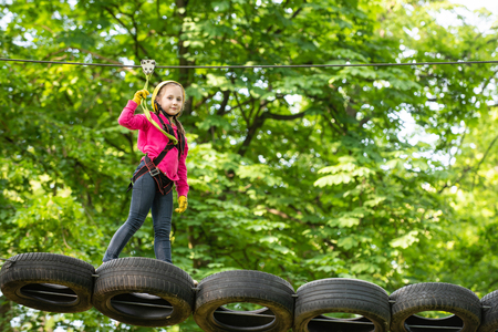 Go Ape Adventure. Toddler climbing in a rope playground structure. Cute child in climbing safety equipment in a tree house or in a rope park climbs the rope.
