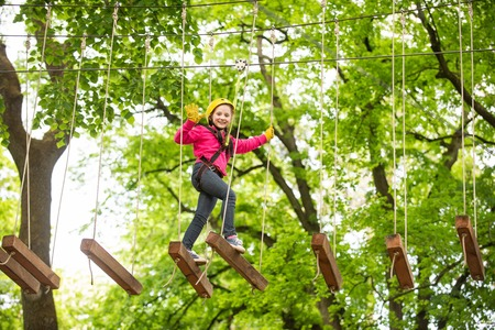 Happy child climbing in the trees. Rope park. Climber child. Early childhood development. Roping park. Balance beam and rope bridges. Rope park - climbing center.
