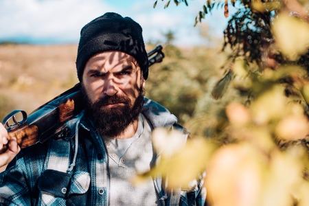 Hunter with shotgun gun on hunt. Close up Portrait of hamdsome Hunter. Man holding shotgun. Track down. Reklamní fotografie