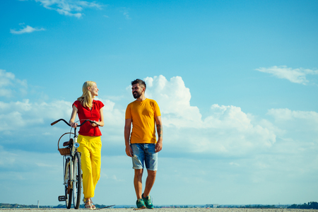 Sky background for your text. Beautiful summer day. Summer vacation. Enjoying time together. Summer couple. Couple in summer dress rides a bike. Talking. Blue sky background - copy space.