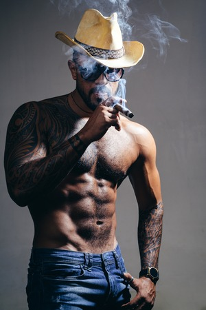health. smoking cigarette. exhale smoke. bad habit. confidence charisma. sexy abs of tattoo man. male fashion. muscular macho man with athletic body. brutal sportsman in cowboy hat. Stock Photo