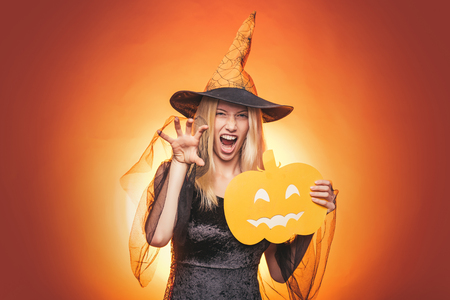 Happy young woman in witch halloween costume on party over isolated background. Emotional young woman in halloween costume on halloween party over white background. Looking camera. Stock Photo