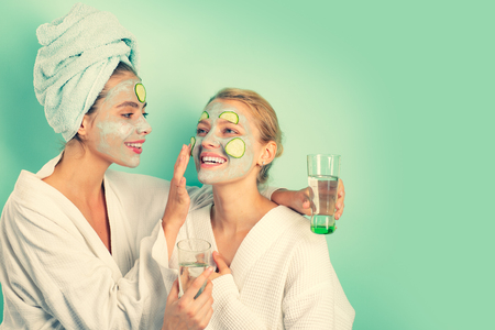 Anti age mask. Stay beautiful. Skin care for all ages. Women having fun cucumber skin mask. Relax concept. Beauty begins from inside. Spa and wellness. Girls friends sisters making clay facial mask Archivio Fotografico