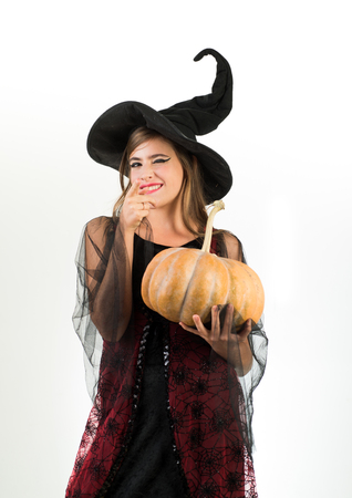Happy young woman in witch halloween costume on party over isolated background. Happy gothic young woman in witch halloween costume with hat standing and smiling over white background. Crazy people. Stok Fotoğraf