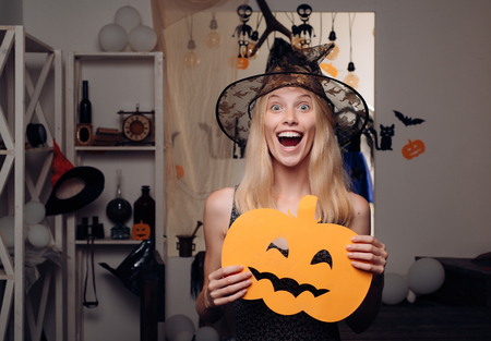 Attraktives vorbildliches Mädchen im Halloween-Kostüm. Halloween-Hexe mit Kürbis. Schöne junge Frau im schwarzen Hexenkostüm mit Hut und Besen, die über orange Hintergrund stehen.