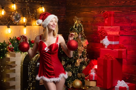 Cute sexy Christmas woman in red lingerie showing Christmas balls. Celebrating noel party. 版權商用圖片 - 125232377