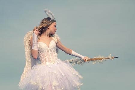 El pequeño Cupido lindo dispara un arco. Cupido en el día de San Valentín. flecha y alas. Tarjeta de amor. Arco y flecha. Encantadora niña rizada en vestido blanco y alas - angel cupid girl Foto de archivo