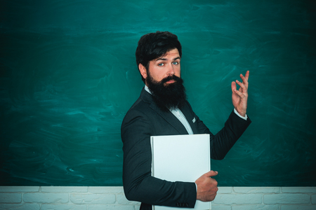Bearded professor at school lesson at desks in classroom. Back to school and happy time. High school concept copy space. Serious male Student studying in school.