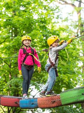 Small boy enjoy childhood years. Happy child boy calling while climbing high tree and ropes. Cute child in climbing safety equipment in a tree house or in a rope park climbs the rope.