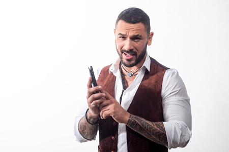 Masculinity concept. Portrait of sexy handsome fashion man model with confident expression, dressed in elegant white shirt, looks at camera, having a phone talk. Brutal bearded boy with tattoo. Attractive elegant male . Old-fashioned clothing, retro style.