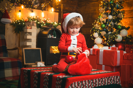christmas stocking. Christmas miracle and new year feelings. A little boy in warm clothes sitting and playing with textile toys. Open-ended Games. First memory of childhood. Фото со стока