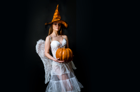 Halloween people in angel costume. Fashion Art Halloween design scene. Halloween Party girl. Female angel girl hold Pumpkin. Halloween girl in costume angel on black background.