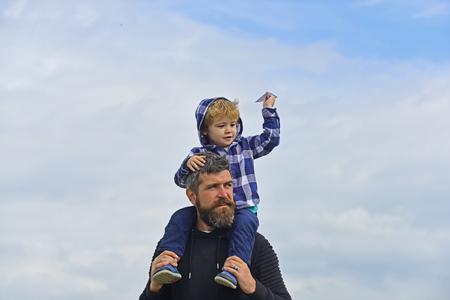 Padre e hijo jugando juntos. Padre y su hijo niño jugando al aire libre. Infancia. Libertad para soñar - niño alegre jugando con avión de papel. Foto de archivo