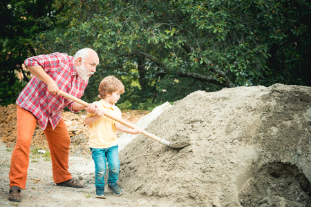 Little son helping his father with building work. Childhood concept. Future worker son with father. Child and works. Little son worker with shovel.
