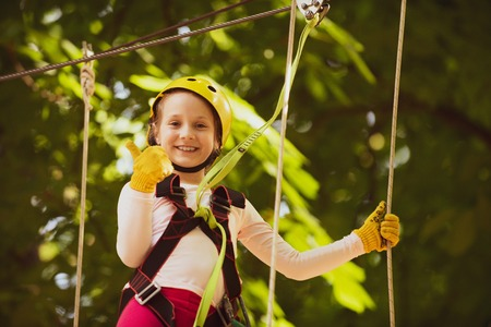 Rope park - climbing center. Artworks depict games at eco resort which includes flying fox or spider net. Hiking in the rope park girl in safety equipment. Roping park. Child.