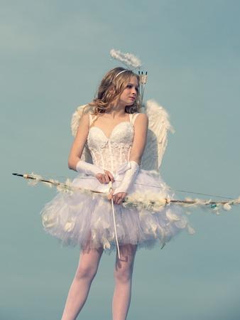 Cupido lindo ángel con arco y flechas. niña Cupido apuntando a alguien con una flecha de amor. Angel niño niña con cabello rubio rizado